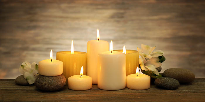 Beautiful composition with candles and spa stones on wooden back